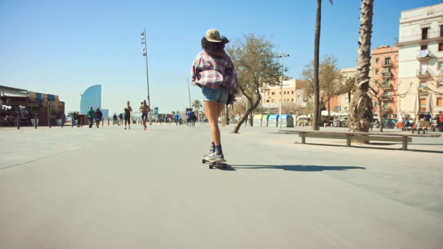 frau am strand skateboarding - barcelona stock-videos und b-roll-filmmaterial