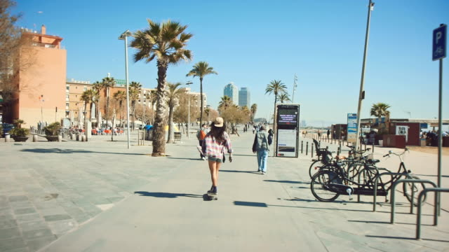 Frau am Strand skateboarding