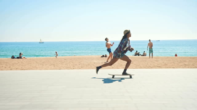 woman skateboarding at beach - sidewalk stock videos & royalty-free footage