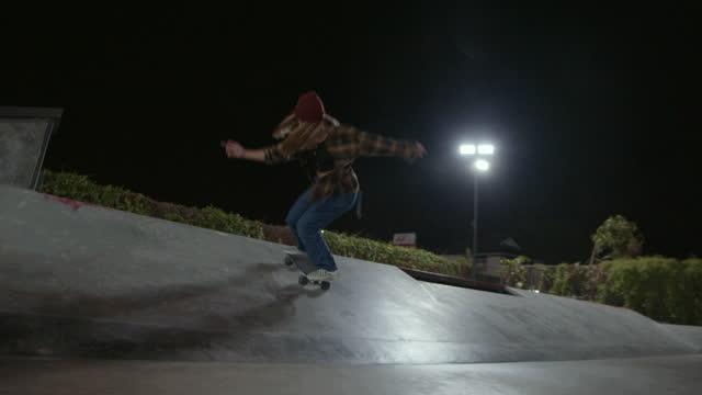 donna che fa skateboard per strada di notte - stunt video stock e b–roll