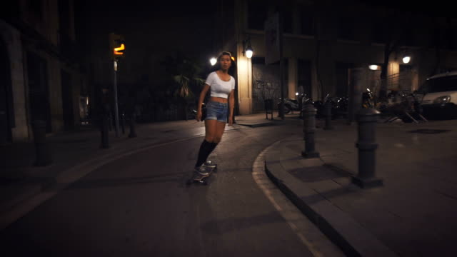 woman skateboarding on street at night - facade stock videos & royalty-free footage