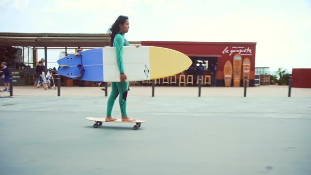 vídeos de stock, filmes e b-roll de mulher andando de skate na rua - diving suit