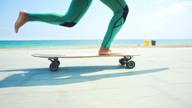 woman skateboarding on street - diving suit stock videos and b-roll footage
