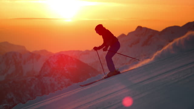 slo mo ts woman skiing as the sun sets - skiing stock videos & royalty-free footage