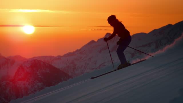 vídeos de stock e filmes b-roll de slo mo ts woman skiing down the slope at sunset - bastão de esqui