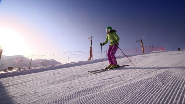 vídeos de stock e filmes b-roll de slo mo woman skiing down the slope in morning sun - bastão de esqui