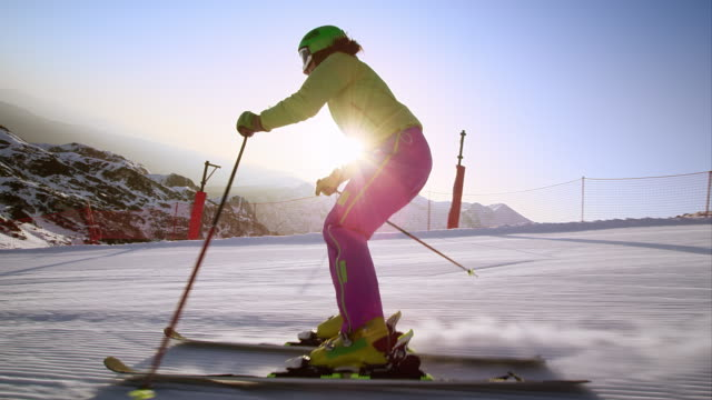slo mo ts woman skiing in early morning sun - skiing stock videos & royalty-free footage