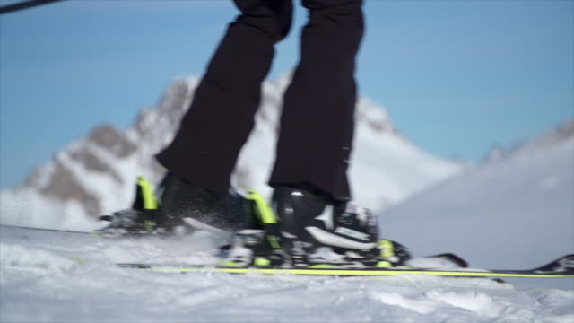 a woman skiing in the snow at a ski resort. - slow motion - skifahren stock-videos und b-roll-filmmaterial