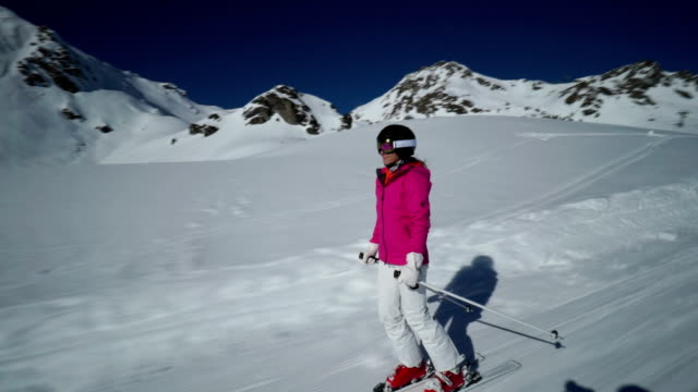 woman skiing on path connecting ski pistes - skijacke stock-videos und b-roll-filmmaterial