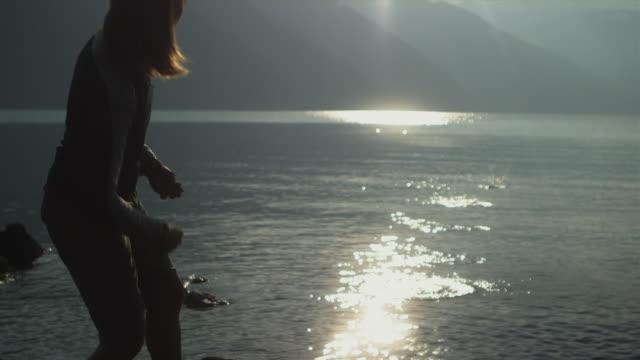 slo mo ms tu td woman skimming pebbles on water surface, garibaldi provincial park, squamish, british columbia, canada - garibaldi park stock videos & royalty-free footage