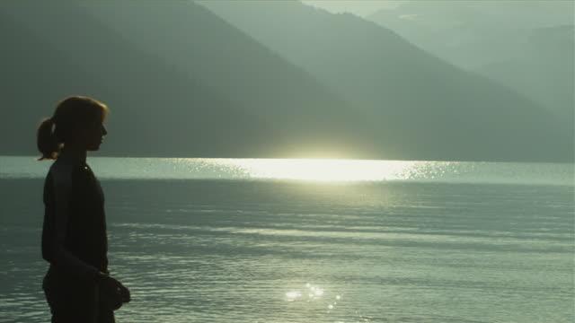 slo mo ms td woman skimming pebbles on water surface, garibaldi provincial park, squamish, british columbia, canada - garibaldi park stock videos & royalty-free footage