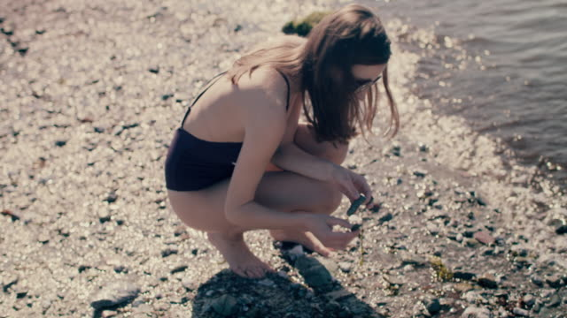 woman skimming stones on beach - crouching stock videos & royalty-free footage