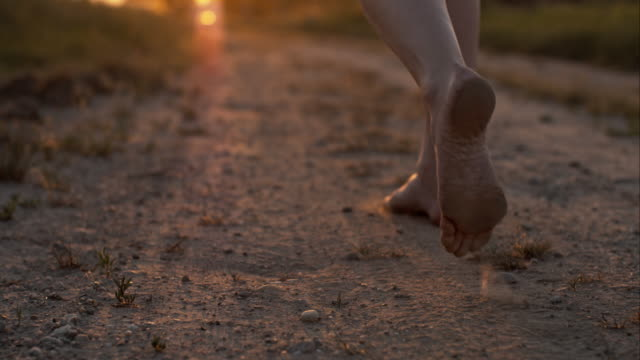 stockvideo's en b-roll-footage met woman skipping barefoot on a dirt road - blootvoets