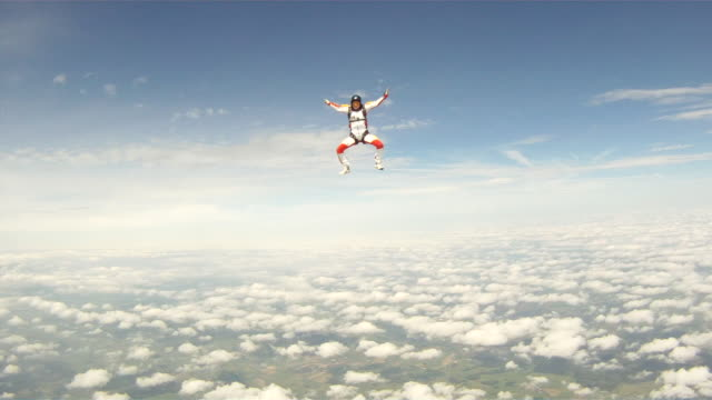vidéos et rushes de woman sky diver performs acrobatic mid-air stunts - parachute