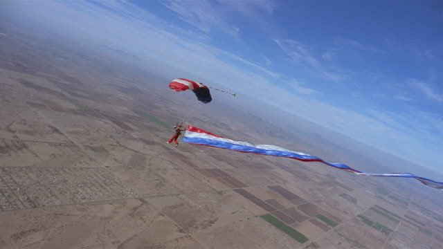 ws woman skydiving and trailing large red, white, and blue streamer behind her in mid air above patchwork landscape / eloy, arizona, usa - patchwork landscape stock videos and b-roll footage