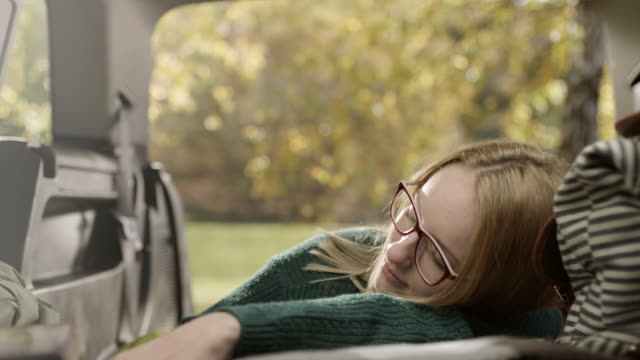 Woman sleeping and dreaming in back of the car