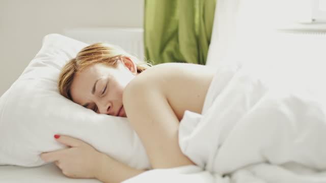 ds kvinna sova bekvämt i sängen på morgonen - endast en kvinna i 30 årsåldern bildbanksvideor och videomaterial från bakom kulisserna