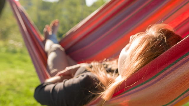 woman sleeping in a swinging hammock in backyard at sunrise - attività del fine settimana video stock e b–roll