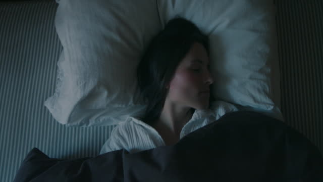 woman sleeping in bed and waking up in morning - junge frauen stock-videos und b-roll-filmmaterial