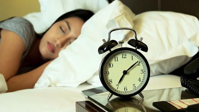 vídeos de stock e filmes b-roll de 4 k : mulher a dormir na cama, desligar o relógio de alarme - edredão