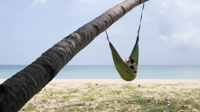 Woman sleeping in hammock hanging from a palm tree