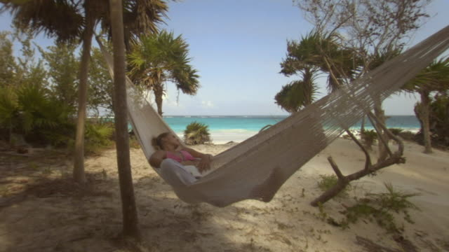 LA MS Woman sleeping in hammock with beach in background/ Tulum, Mexico
