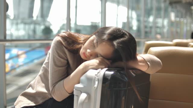 vídeos de stock, filmes e b-roll de mulher dormindo no aeroporto - chegada