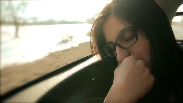 Frau schläft im Auto auf dem Rücksitz
