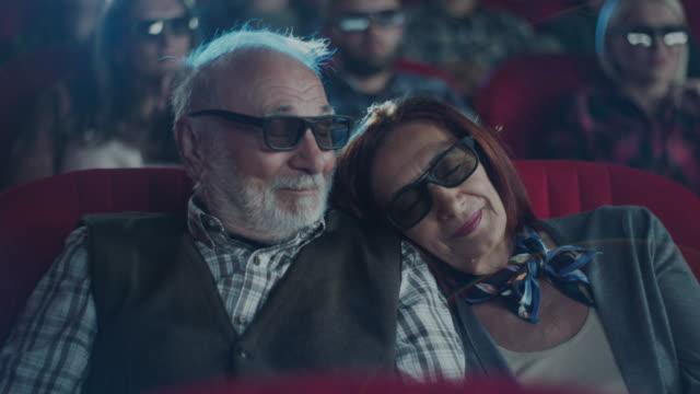 frau schläft auf der schulter des mannes im kino - paar gruppierung stock-videos und b-roll-filmmaterial