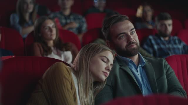 frau schläft auf der schulter des mannes im kino - filmindustrie stock-videos und b-roll-filmmaterial