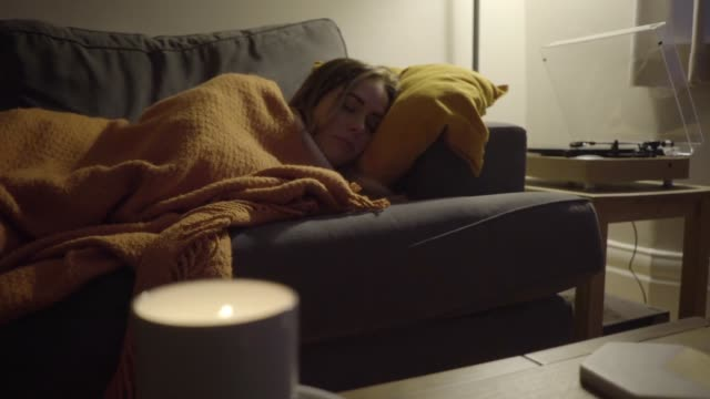 vídeos de stock e filmes b-roll de woman sleeping on sofa as record plays at night - sofá