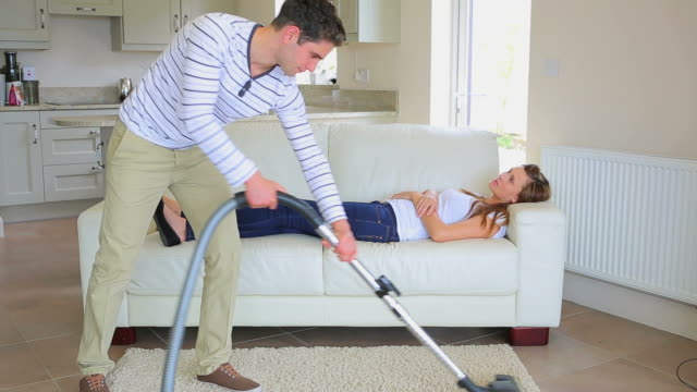 woman sleeping on the sofa while man doing the housework - housework stock videos and b-roll footage