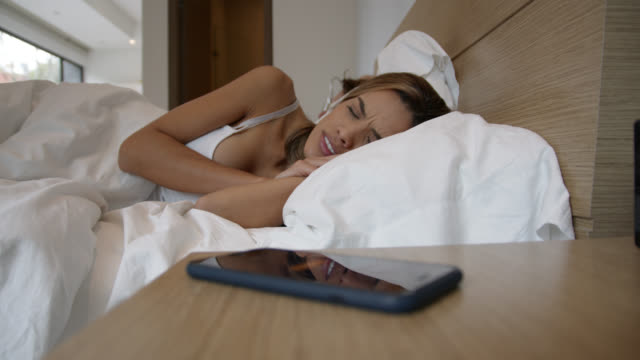 woman sleeping with her partner in bed postponing her alarm from smartphone - allarme video stock e b–roll