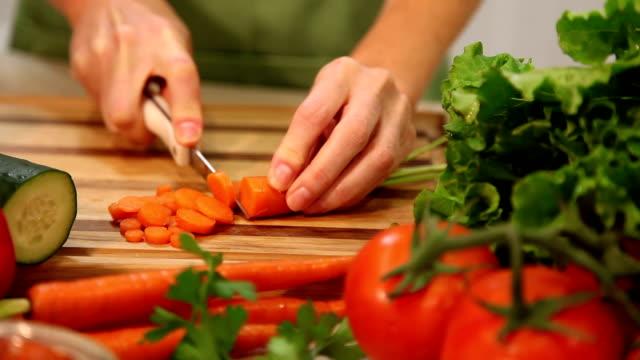 donna fette carote e verdure in cucina di casa. - cucina vegetariana video stock e b–roll