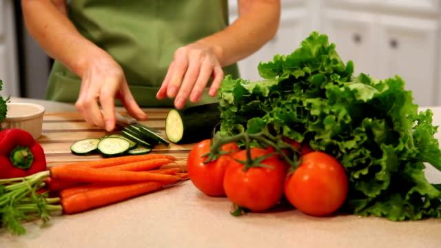 Donna fette di cetriolo, verdure in cucina di casa.