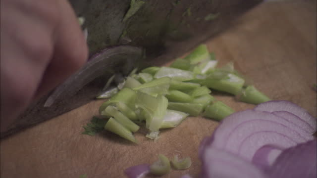 Woman slices spring onion with a cleaver, Beijing.