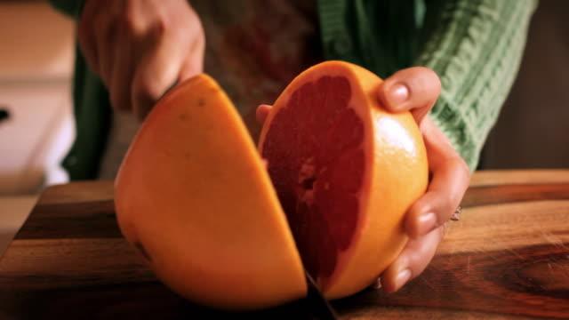 CU TU TD Woman slicing grapefruit / New York City, New York, USA