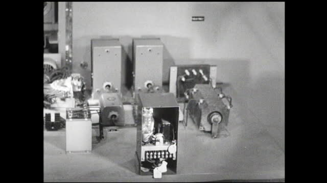 vidéos et rushes de woman sliding components into metal casing; woman assembling components at workstation; man showing another man how to solder; woman connecting wires... - 1940 1949