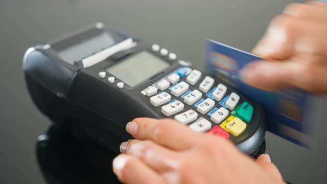 Woman sliding credit card in POS terminal, entering PIN code