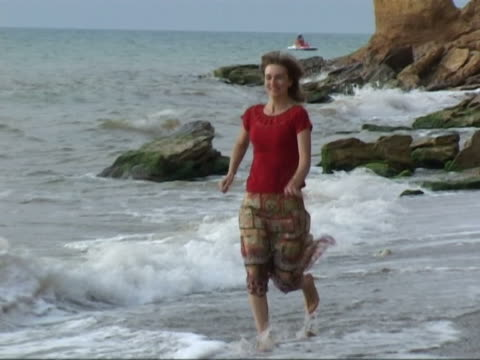 stockvideo's en b-roll-footage met woman slowly running on the beach - jogster
