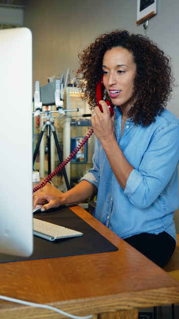 a woman small business owner talking on the telephone and working on her computer - landline phone stock videos & royalty-free footage