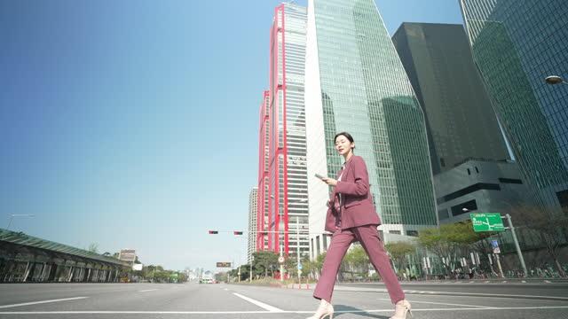 vidéos et rushes de woman smart life - businesswoman crossing road while using smart phone - quartier