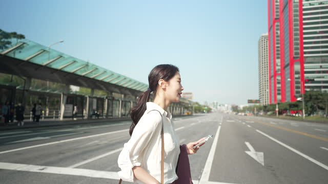woman smart life - businesswoman crossing road while using smart phone - road signal stock videos & royalty-free footage
