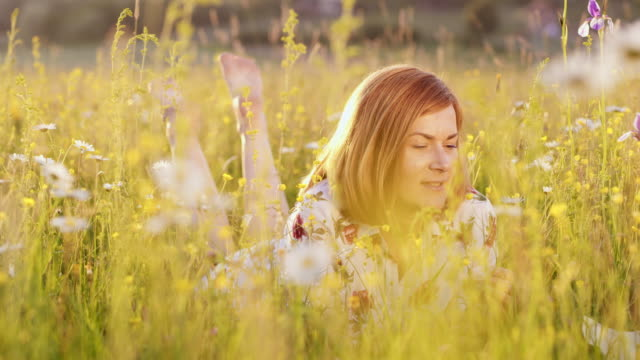 ds woman smelling a daisy in the middle of a spring meadow - slovenia meadow stock videos & royalty-free footage