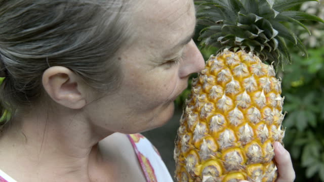 woman smelling a pineapple - pineapple stock videos & royalty-free footage