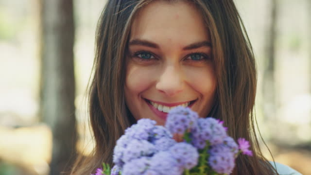 woman smelling at flowers - springtime stock videos & royalty-free footage