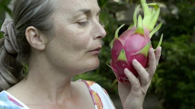 stockvideo's en b-roll-footage met woman smelling dragon fruit, pitaya (hylocereus undatus) - vetplant
