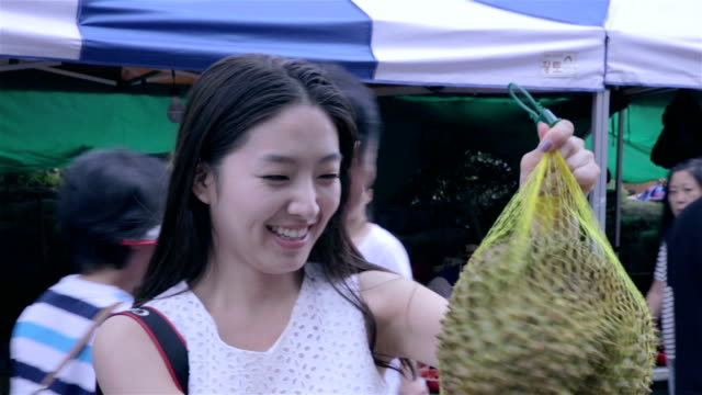 Woman smelling stinky Durian fruit in a market