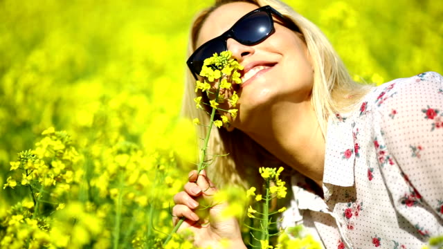 Woman smelling yellow flowers.