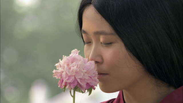 Woman smells flower.